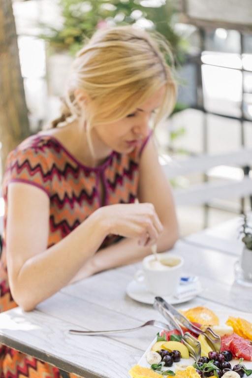 Devojka uživa u jutarnjoj espreso kafi i svežem voću
